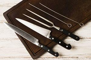 Deux couteaux et des piques à brochette sur une planche à coupe